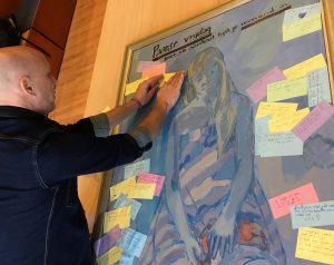 Jan Willem plakt de tips van de leerlingen op het schilderij